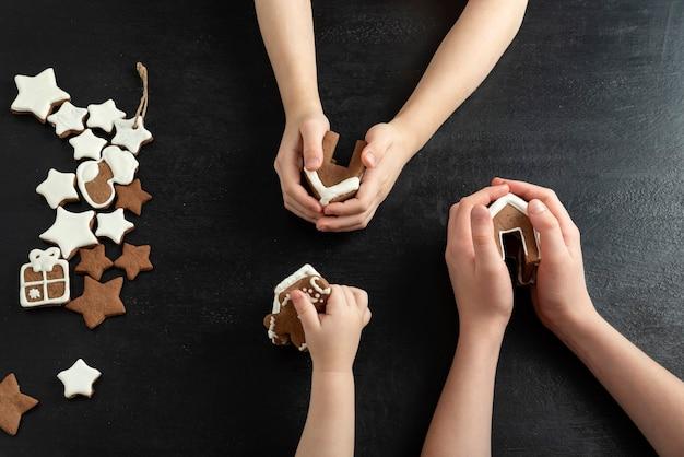 Domki z piernika i gwiazdki ciasteczka w rękach dzieci. czarne tło, widok z góry.