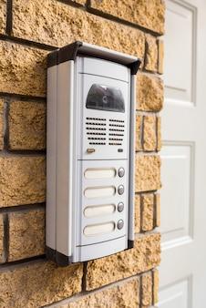 Domofon na ścianie z cegły przy drzwiach