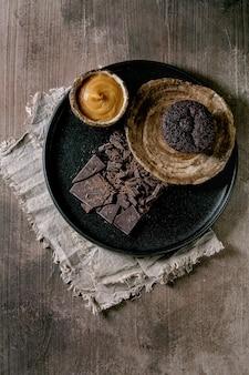 Domowa babeczka czekoladowa z sosem ze słonego karmelu i posiekaną gorzką czekoladą na czarnym talerzu ceramicznym nad betonowym stołem. leżał płasko, kopia przestrzeń