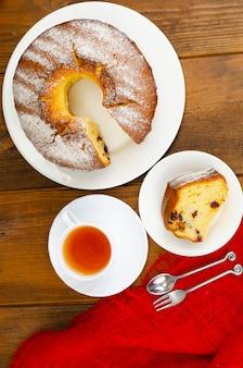 Domowa babeczka z suszonymi jagodami i cukrem pudrem na talerzu