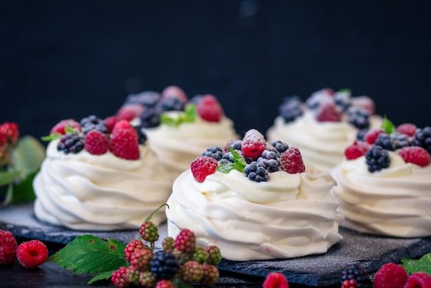 Domowa baza bezowa do ciasta pavlova ze świeżymi jagodami i blackberry oraz cukrem pudrem na czarnej betonowej teksturze
