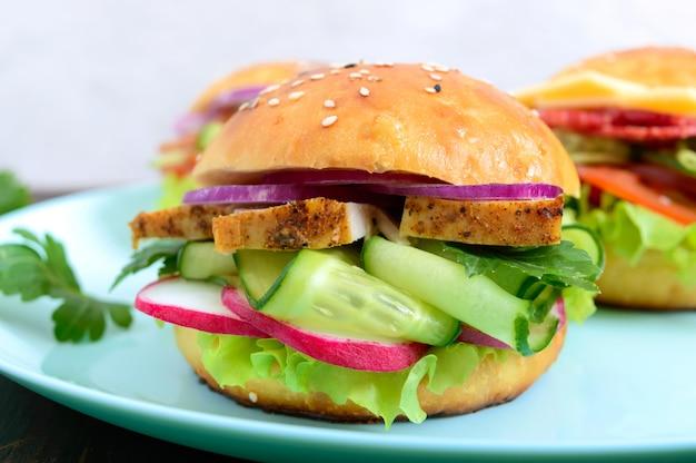 Domowa bułka z piersią indyka, warzywami, ziołami na drewnianej desce. kanapka na lunch. ścieśniać