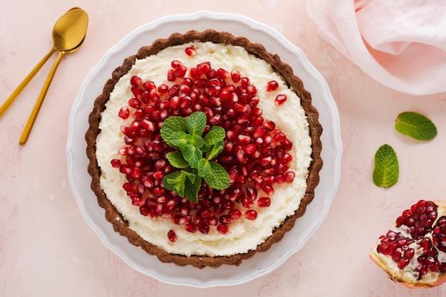 Domowa deserowa tarta czekoladowa z kremem kokosowym i granatem oraz miętą na różowej powierzchni stołu