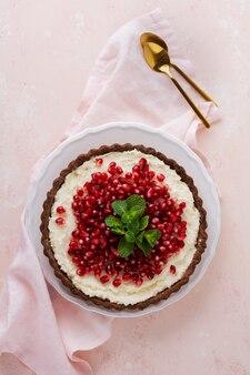 Domowa deserowa tarta czekoladowa z kremem kokosowym i granatem oraz miętą na różowym tle stołu. widok z góry.
