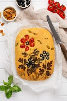 Domowa focaccia kwiatowa. kreatywny pomysł na gotowanie focaccia. chrupiąca focaccia z warzywami. widok z góry.