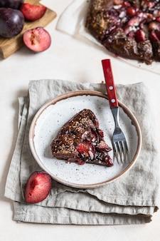 Domowa galette lub otwarte ciasto z czekoladą, śliwką i migdałami na jasnym betonowym tle.