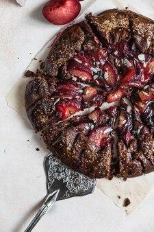 Domowa galette lub otwarte ciasto z czekoladą, śliwką i migdałami na jasnym tle. widok z góry.