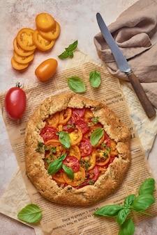 Domowa galette lub pikantne ciasto z czerwonymi i żółtymi pomidorami i bazylią na starej gazecie lub pergaminie. widok z góry.
