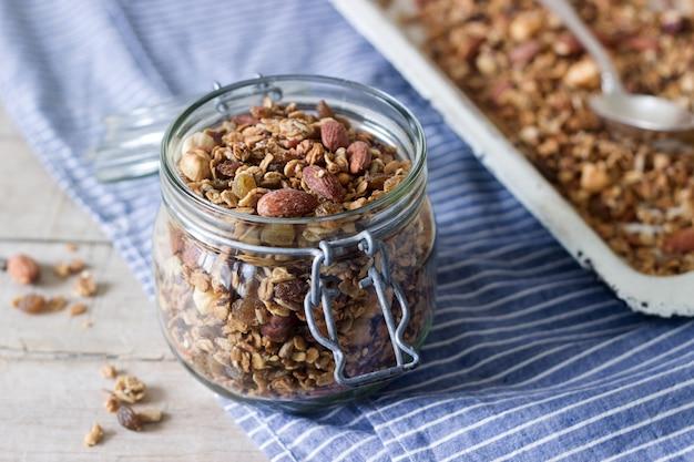 Domowa granola w szklanym słoju i na blasze do pieczenia.