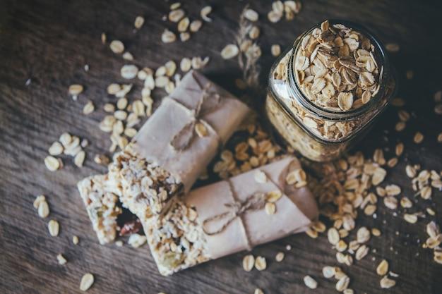 Domowa granola z mieszanką orzechów w szklanym słoju na drewnianej desce