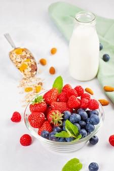 Domowa granola z orzechami, suszonymi owocami i świeżymi jagodami.