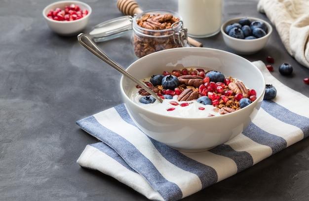 Domowa granola z pestkami granatu jagodami orzechami pekan i jogurtem na betonowym tle