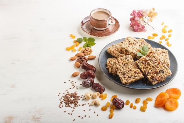 Domowa granola z płatków owsianych, daktyli, suszonych moreli, rodzynek, orzechów w niebieskim talerzu ceramicznym. widok z boku.