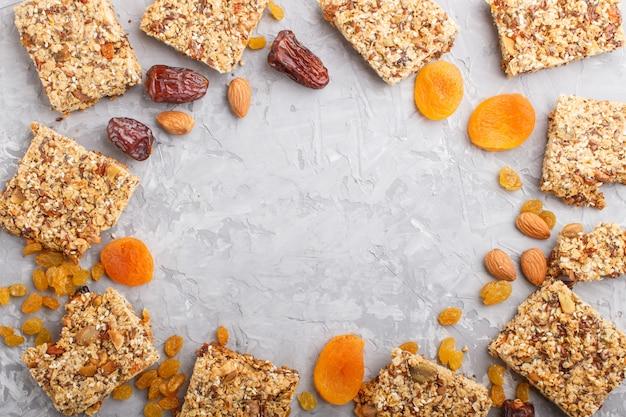 Domowa granola z płatków owsianych, daktyli, suszonych moreli, rodzynek, orzechów z filiżanką kawy na szarym betonowym tle