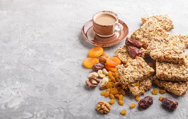 Domowa granola z płatków owsianych, daktyli, suszonych moreli, rodzynek, orzechów z filiżanką kawy. widok z boku