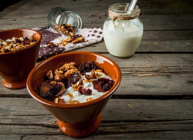Domowa granola z suszonymi owocami i orzechami, jogurt organiczny w słoiku.