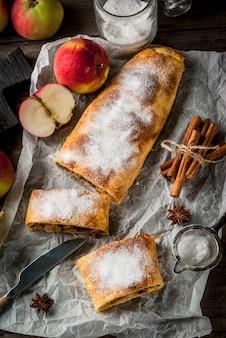 Domowa jesień, letnie wypieki, ciasta francuskie. strudel jabłkowy z orzechami, rodzynkami, cynamonem i cukrem pudrem. na drewnianym starym rustykalnym stole. w plasterkach, ze składnikami. skopiuj widok z góry