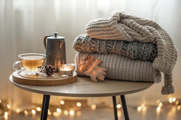 Domowa jesienna kompozycja z herbatą i sweterkami z dzianiny we wnętrzu pokoju, na rozmytym tle z girlandą.