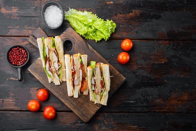 Domowa kanapka klubowa z indykiem, bekonem, szynką, pomidorami, na starym drewnianym stole, widok z góry z miejscem na tekst