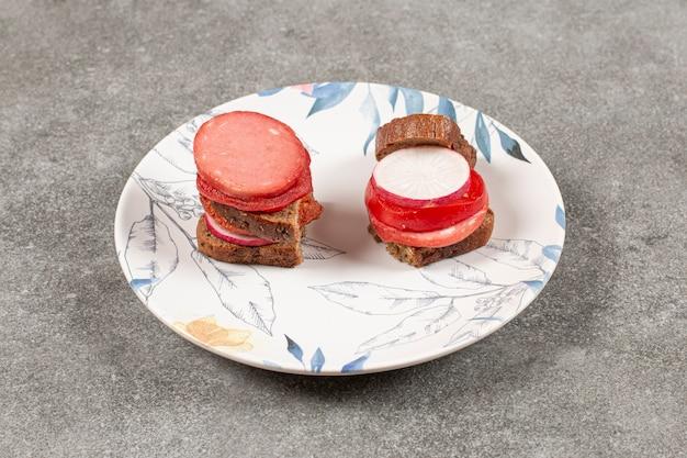 Domowa kanapka. salami, chleb żytni i warzywa na białym talerzu.