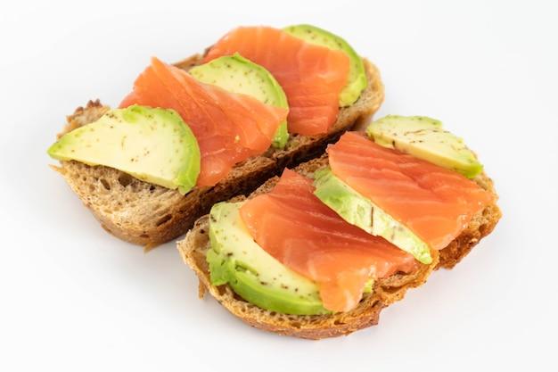 Domowa kanapka tostowa z łososiem i awokado na kromce chleba zbożowego. zdrowe jedzenie.