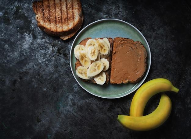 Domowa kanapka vagan z masłem orzechowym i bananem podana na ceramicznym talerzu nad rustykalnym stołem. koncepcja śniadanie wegańskie. widok z góry. flat lay