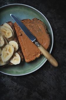 Domowa kanapka vagan z masłem orzechowym i bananem podana na ceramicznym talerzu z zabytkowym nożem nad rustykalnym stołem. koncepcja śniadanie wegańskie. widok z góry. flat lay
