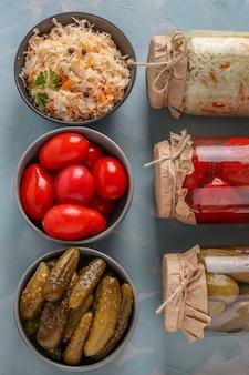 Domowa kapusta kiszona, solone pomidory i ogórki w miskach i szklane słoiki na jasnoniebieskim tle, warzywa fermentowane koncepcyjnie, orientacja pionowa