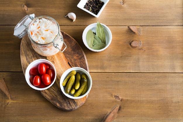 Domowa kapusta kiszona w szklanym słoju i miseczkach z marynowanymi ogórkami i pomidorami płasko leżała na drewnianym tle z miejscem na kopię.