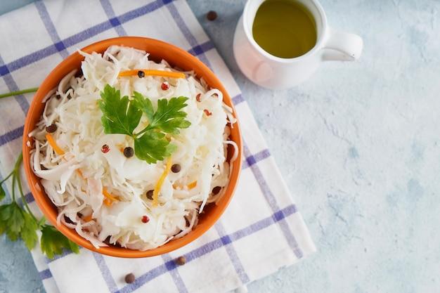 Domowa kapusta kiszona z przyprawami w pomarańczowej misce. naturalne probiotyki, zdrowe jedzenie