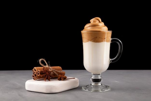 Domowa kawa dalgona w przezroczystej szklanej filiżance z dodatkami. przepis na popularny koreański napój latte z pianką z kawy rozpuszczalnej.