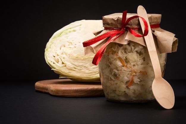 Domowa kiszona kapusta w szklanym słoju na drewnianej desce do krojenia w czarnym tle. świeża główka kapusty na tle... sałatka wegańska. danie jest bogate w witaminę u. jedzenie świetne dla dobrego zdrowia.