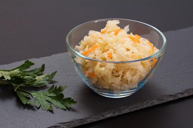 Domowa kiszona kapusta z marchewką w szklanej misce na czarnym tle. sałatka wegańska w stylu rustykalnym. danie jest bogate w witaminę u. jedzenie świetne dla dobrego zdrowia.