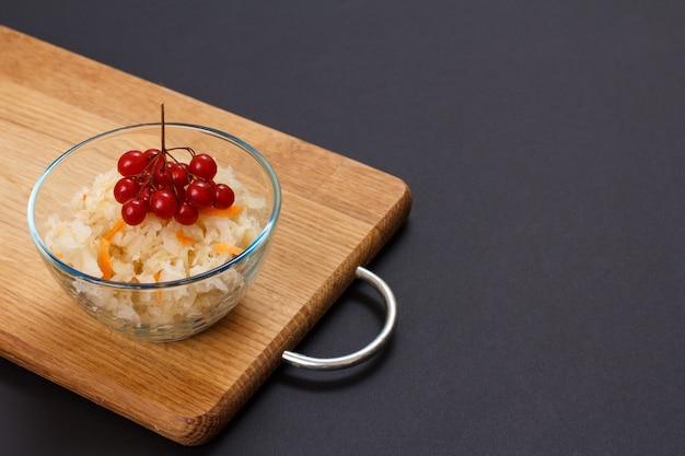 Domowa kiszona kapusta z marchewką w szklanej misce ozdobiona gronem kaliny na desce do krojenia w czarnym tle. sałatka wegańska. danie jest bogate w witaminę u. jedzenie świetne dla dobrego zdrowia.