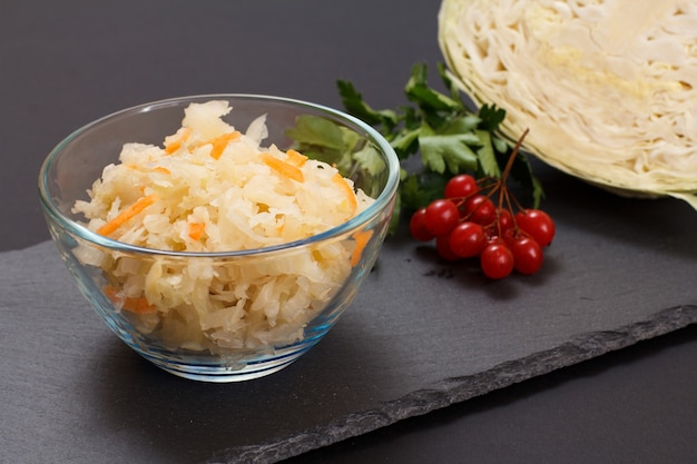 Domowa kiszona kapusta z marchewką w szklanej misce. świeża głowa kapusty i grona kalina na tle. sałatka wegańska. danie jest bogate w witaminę u. jedzenie świetne dla dobrego zdrowia.