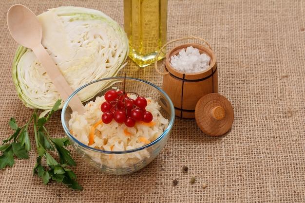 Domowa kiszona kapusta z marchewką w szklanej misce, świeża główka kapusty, sól i butelka oleju na worze. sałatka wegańska. danie jest bogate w witaminę u. jedzenie świetne dla dobrego zdrowia.