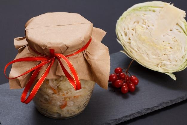 Domowa kiszona kapusta z marchewką w szklanej puszce. świeża głowa kapusty i grona kalina na tle. sałatka wegańska. danie jest bogate w witaminę u. jedzenie świetne dla dobrego zdrowia.