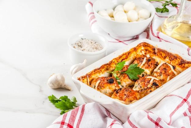 Domowa kolacja zdrowej diety, przygotowane klopsiki z indyka z kurczaka z sosem, serem, zieleniną. na białym marmurowym stole z przyprawami.