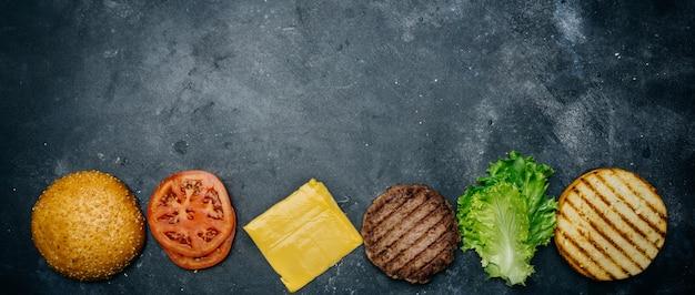 Domowa kompozycja burger (przepis). produkty do klasycznego burgera na ciemnym tle.