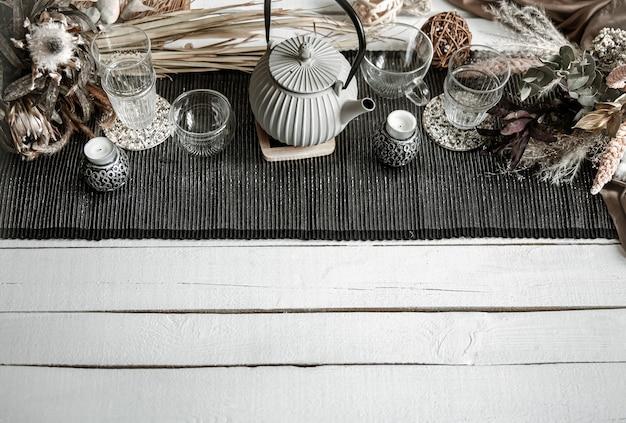 Domowa kompozycja z czajnikiem, szklankami i wieloma dekoracyjnymi detalami na drewnianym stole.