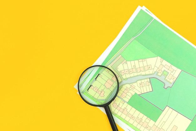 Domowa koncepcja audytu i zakupu nieruchomości płaski leżał backrgound, mapa katastralna z lupą, widok z góry, działka budowlana zdjęcia gruntu