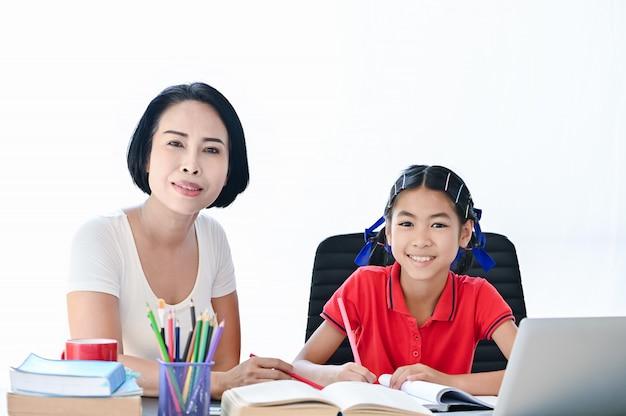 Domowa koncepcja szkoły, azjatyckie dzieci i matka uczą, robiąc szkolną pracę domową, uśmiechając się