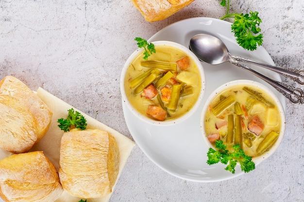 Domowa kremowa zupa jarzynowa na białej misce z bułką i łyżką.