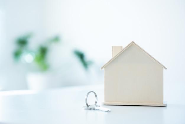 Domowa kształt zabawka z breloczkiem na bielu stołowym i pustym tle.