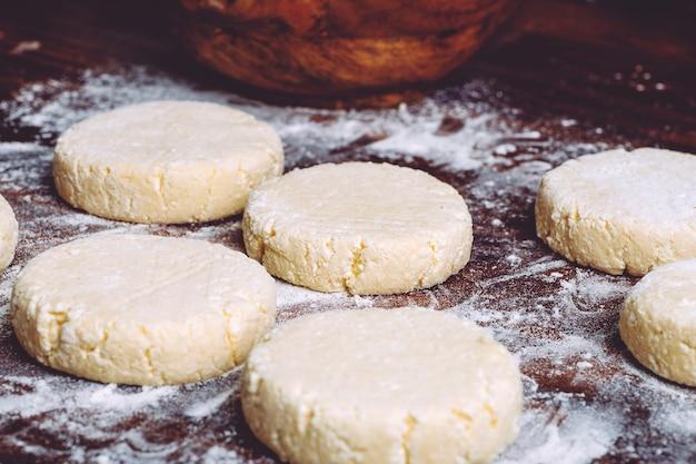 Domowa kuchnia i jedzenie. placki z twarogu na surowo. tradycyjne naleśniki z twarogiem na śniadanie w rosji, na ukrainie i w europie.