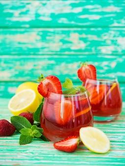 Domowa lemoniada truskawkowa na rustykalnym tle, orzeźwiający letni napój, selektywne skupienie