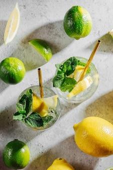 Domowa lemoniada w eleganckich szklankach z cytrynami i limonkami na białym marmurowym tle