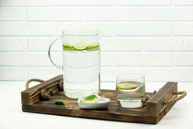 Domowa lemoniada z limonki stoi w szklance i dzbanku na drewnianej tacy