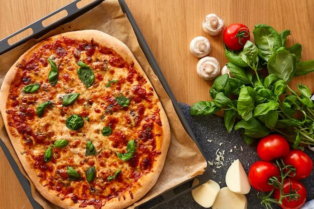 Domowa margarita flatbread pizza z pomidorem i bazylią.