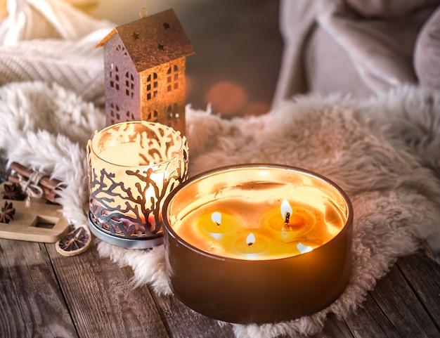 Domowa martwa natura we wnętrzu z pięknymi świecami, na tle przytulnego wystroju domu